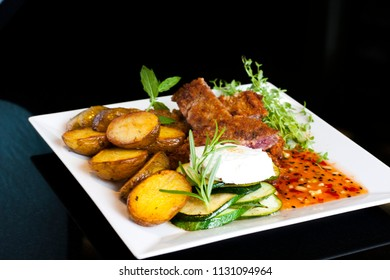 Medium grilled pork chop steak in a white plate  with baked potatoes and vegetable salad on side