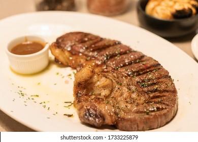 Medium grilled strip loin beef steak with pepper sauce in warm light at restaurant.