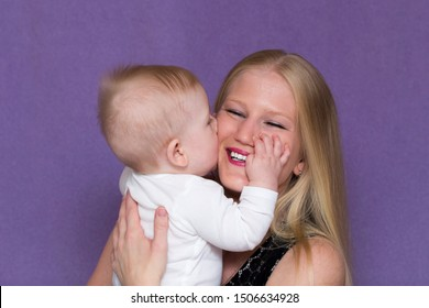 Medium horizontal portrait of adorable happy baby boy kissing his pretty smiling young blond mother holding him against mauve background
