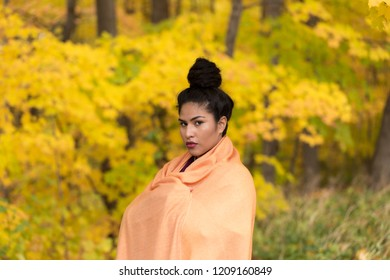 Medium horizontal portrait of sultry hispanic young woman with hair up in a high bun draped in an orange shawl in front of soft focus Fall foliage
