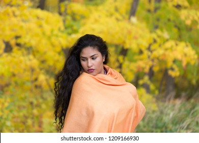 Medium horizontal portrait of sultry hispanic young woman with long dark curly hair draped in an orange shawl looking down in front of soft focus Fall foliage