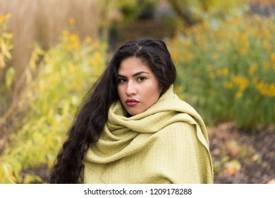 Medium horizontal portrait of sultry hispanic young woman with long curly dark hair draped in pale green shawl in front of soft focus Fall foliage