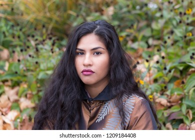 Medium horizontal portrait of sultry hispanic young woman with long curly dark hair wearing elegant bronze top in front of soft focus Fall foliage