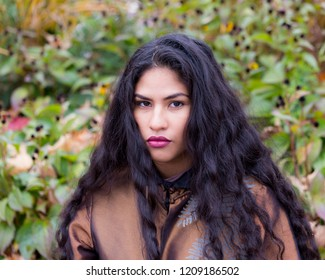 Medium horizontal portrait of sultry hispanic young woman with long flowing curly dark hair wearing elegant bronze top in front of soft focus Fall foliage