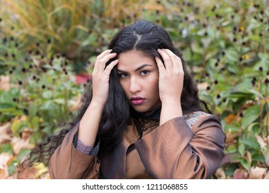 Medium horizontal portrait of sultry hispanic young woman in elegant bronze top pushing her long flowing curly dark hair out of her face in front of soft focus Fall foliage
