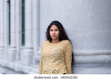 Medium horizontal portrait of sultry hispanic young woman with long curly dark hair wearing elegant gold lace top leaning against stone column with building in soft focus background