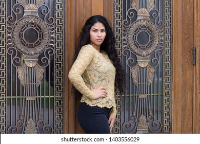 Medium horizontal portrait of sultry hispanic young woman with long curly dark hair wearing elegant gold lace top and tight black jeans posing in front of patrimonial door with ornate window grate