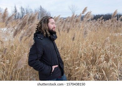 Medium horizontal side view of young bearded man in dark jacket and long hair tied back staring away in a field during a early winter grey windy afternoon, Quebec City, Quebec, Canada