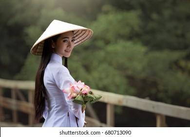 Medium long shot beautiful woman wearing Ao Dai Vietnam traditional dress holding lotus flower