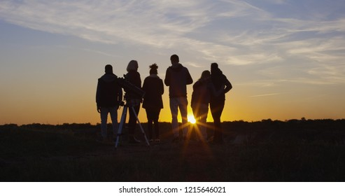 Medium long shot from behind of a group of friends together in the setting sun cheering with raised hands