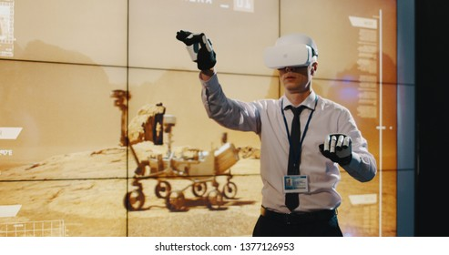 Medium long shot of technician using VR headset and exoskeleton gloves in front of a screen
