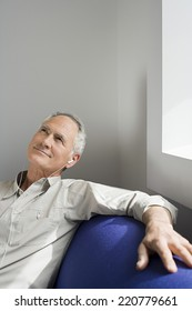 Medium portrait of man enjoying listening to music on headphones seated on sofa