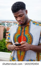 medium portrait shot of Young Mali inmigrant wearing traditional clothes on european country focusee in the phone device shot with a worried and serious face while using smartphone o a city rooftop.