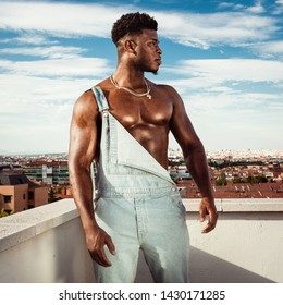 Medium profile shot of a black man wearing an unfastened jean overall on a city rooftop and sky background on a serious and pride mood showing his bright fitness muscles.