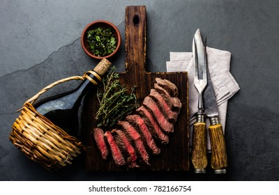 Medium rare beef steak on wooden board with herb sauce chimichurri and botlle of wine