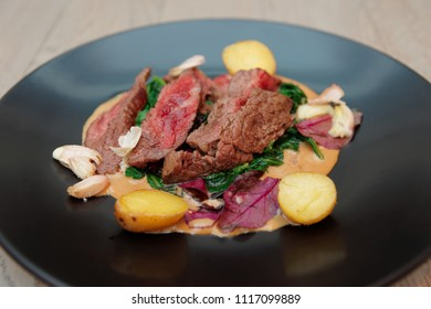 Medium rare fried steak with garlic and potatoes in black plate