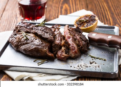 Medium rare grilled marinated beef flank steak on silver plate