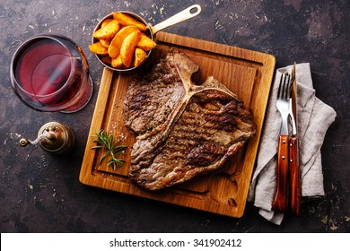 Medium rare Grilled T-Bone Steak with potato wedges and wine on serving board block on dark background