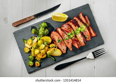 Medium rare meat hanger steak with brussels sprouts, potatoes and onion with herb sauce on a white wooden table. Delicious healthy food. Top view above.