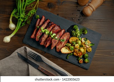 Medium rare meat hanger steak with brussels sprouts, potatoes and onion with herb sauce on a table.. Delicious healthy food. Top view above.