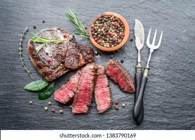 Medium rare Ribeye steak with herbs on graphite board. Top view.