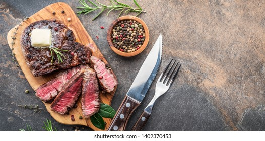 Medium rare Ribeye steak with herbs and a piece of butter on the wooden tray. Top view.