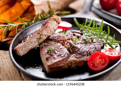 Medium rare roast beef with potato over black stone background. Top view, flat lay