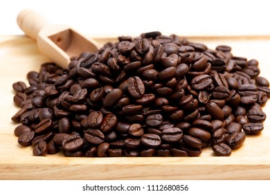 Medium roasted organic coffee beans on wooden plate close up.