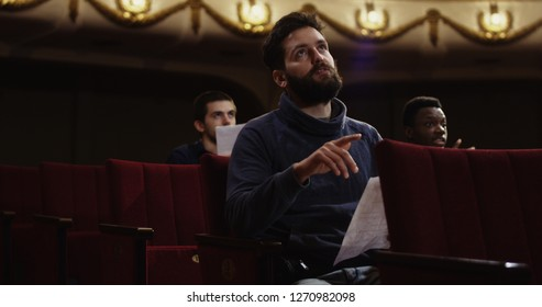 Medium shot of an actor rehearsing singing in the theater
