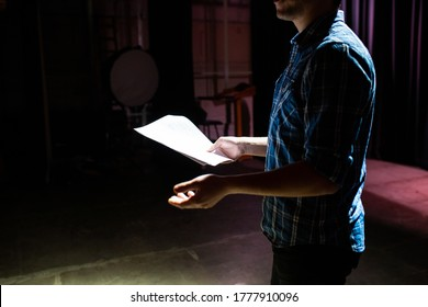 Medium shot of actors and actresses rehearsing a scene in a theater. Medium shot of an actor performing a monologue in a theater while holding his script