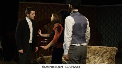 Medium shot of actors performing a scene where a woman mediating between two quarreling men