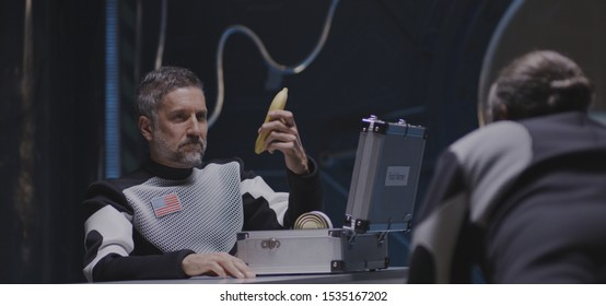 Medium shot of an astronaut pushing a banana through the air in zero gravity to his comrade