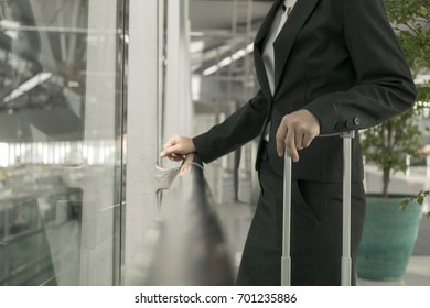 Medium shot : Businesswoman standing holding luggage at the airport.