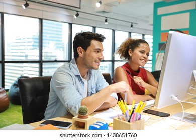 medium shot of caucasian graphic design and coworker in smart casual wear talking and working on computer in creative office with happy and smiling face