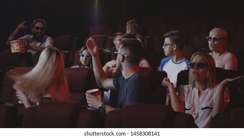 Medium shot of cinema audience throwing popcorn at young man spoiling the movie in a cinema