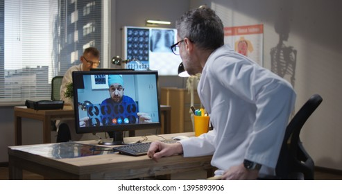 Medium shot of doctors discussing MRI scan results during a video call