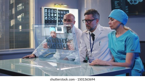 Medium shot of doctors using a holographic display screen for a video call