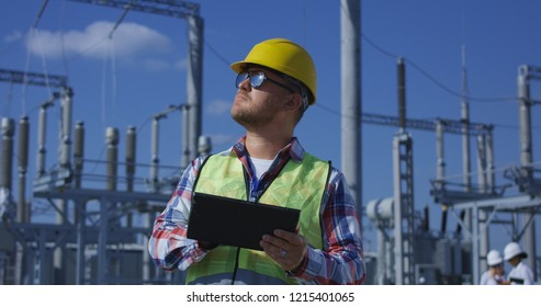Medium shot of an electrical worker reviewing documents on a tablet during an inspection against the background of a transformer station