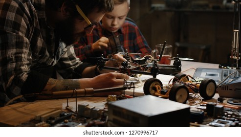 Medium shot of a father and son repairing a drone with wireless control in a garage