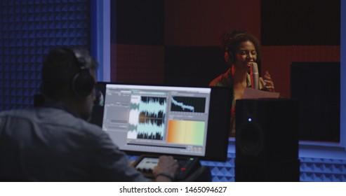 Medium shot of a female actor doing voice over in studio
