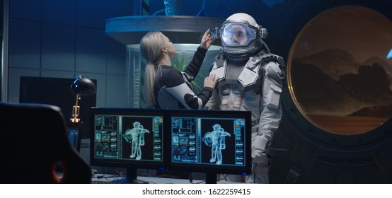 Medium shot of a female astronaut helping her comrade to turn on lamps and camera on his spacesuit