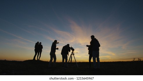 Medium shot of friends stargazing together and using a professional telescope at night near a stream