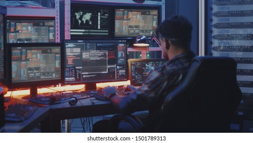Medium shot of a hacker watching multiple monitors while working