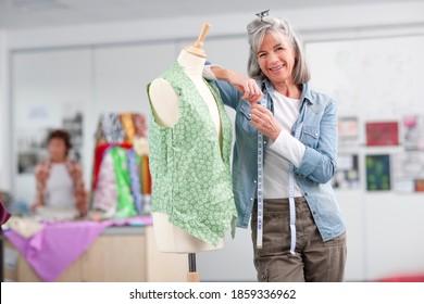 A medium shot of a happy senior female designer leaning on a dressmakers dummy in a classroom.