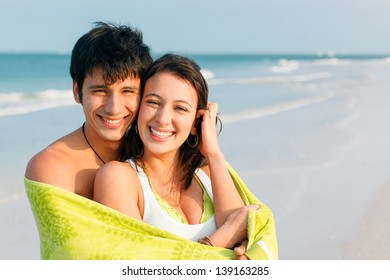 Medium shot of happy, smiling young latin couple on Beach wrapped in Green Towel. Ft. DeSoto Beach, Florida, USA.