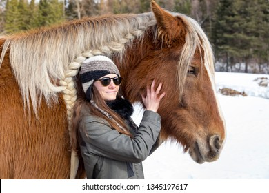 Medium shot of long-haired brunette smiling young woman in warm clothes and sunglasses petting sturdy tall rust coloured horse against winter countryside landscape