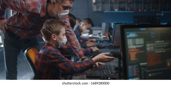 Medium shot of a male student and a teacher in face masks discussing programming in school