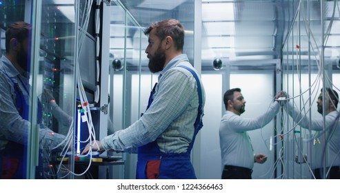 Medium shot of a manager and technician working in a data center with cable to repair rows of server racks and discuss their work