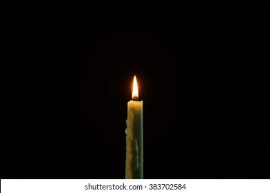 Medium shot on blue green candle on black background. Thin blue green candle lighted.