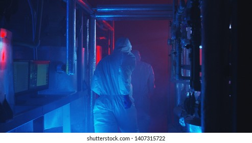 Medium shot of scientists fleeing from scene of an industrial accident when alarming red light starts flashing